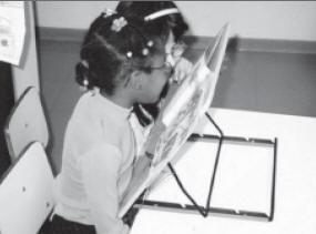 criança com baixa visão lê com auxílio de um atril