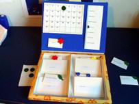 Elementos que conforman el calendario de nivel 2: panel con mes completo, días de la semana, y caja con tarjetas y gomets.
