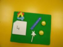 Tablilla de franela con una etiqueta con el número 4, una varita mágica, dos bolas, etc.