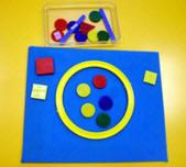 Franelograma cuadrado con distintos objetos geométricos adheridos a él, más una caja con otros elementos geométricos.