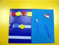 Franelograma cuaderno, abierto y con distintos objetos geométricos adheridos a ella sobre unas tiras de velcro.