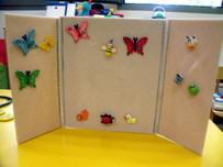 Franelograma tríptico, abierto y en posición vertical, con varias mariposas y otros animalillos adheridos a él.