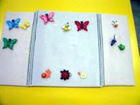 Franelograma tríptico extendido sobre una mesa en posición horizontal, con varias mariposas y otros animales adheridos a él.
