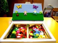 Franelograma caja de artista mostrando el lado con dos piezas y dos huecos con elementos para realizar composiciones.