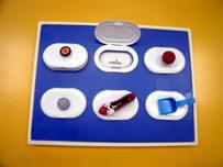Tablero con seis huecos, cada uno de ellos con un objeto pegado a la tapa y una nota escrita en su interior.