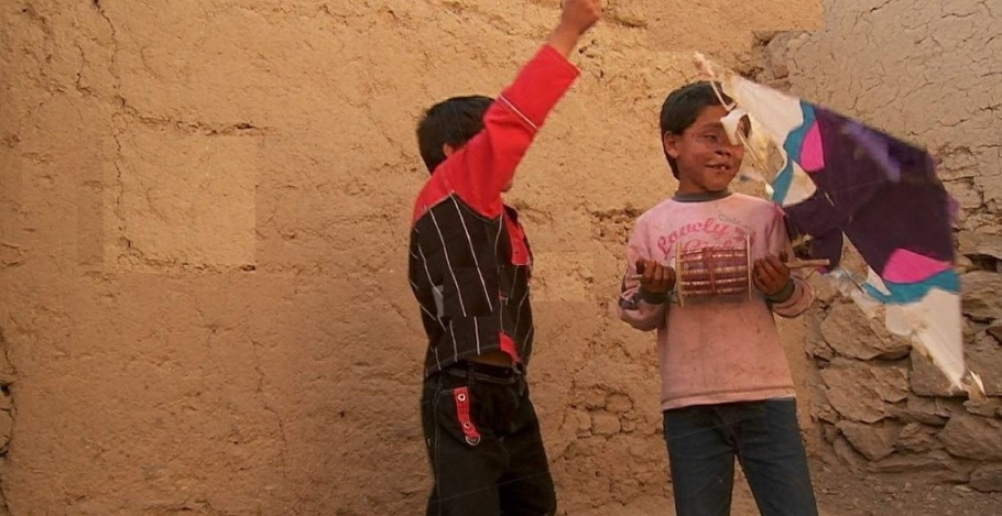 Blind child & friend play with a broken kite in Kabul